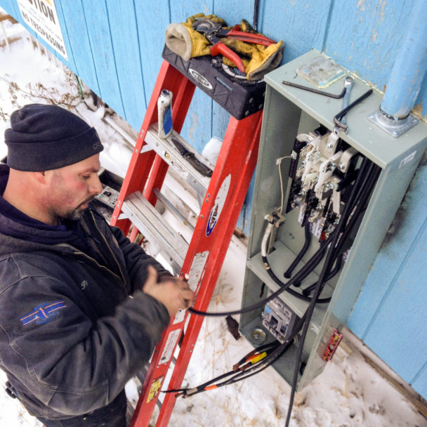 Nome electrician Pat Knodel replacing parts on KNOM's AM transmitter power panel.