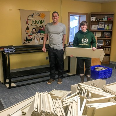 Nome Community Baptist Church Pastor Dan Heihn and volunteer Tyler Stup, sorting out the recycled shelves donated to KNOM.