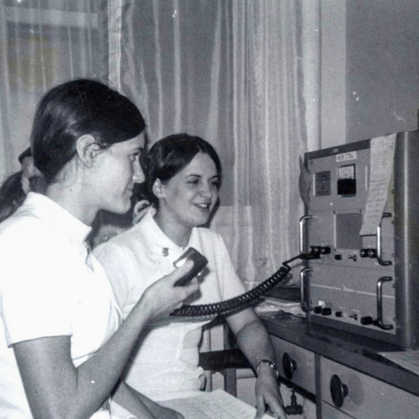Black and white photo of two nurses, Candy Gleason and Meg Gabriel, consulting with a village health aide using short wave radio.