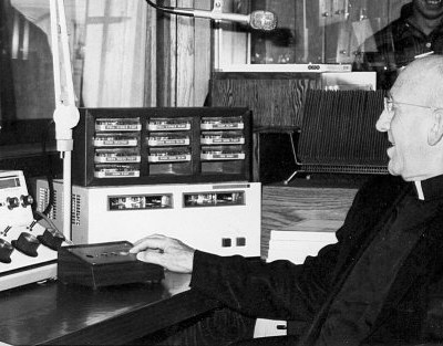 Black and white image of Catholic bishop pushing button on radio control console