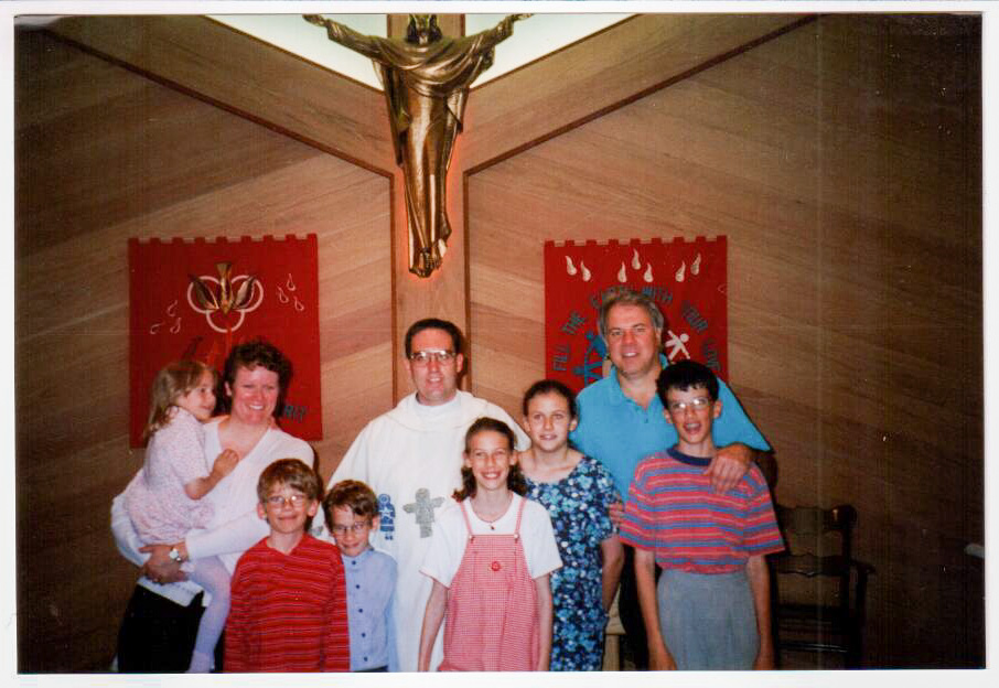 Ric, Lynette, and their children pose with Father Ross Tozzi inside a Catholic church.