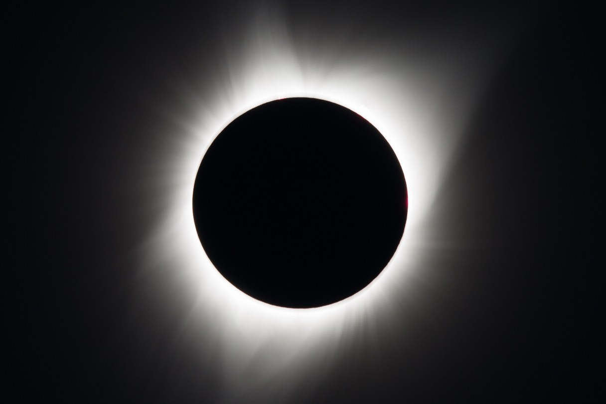 A total solar eclipse: a black sky with the sun completely blocked by the moon in silhouette, leaving only the white corona of the sun visible.