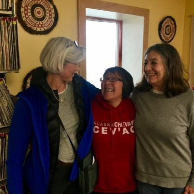 Tandy Wallack, Etta Tall, and documentary filmmaker Lourdes Grobet laugh together in the the KNOM studios, where they stopped by before heading to Little Diomede for a long-awaited family reunion.