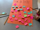 """Brightly colored sticky notes cover a poster labeled """"How to help,"""" where they brainstormed ideas for supporting friends going through a hard time."""