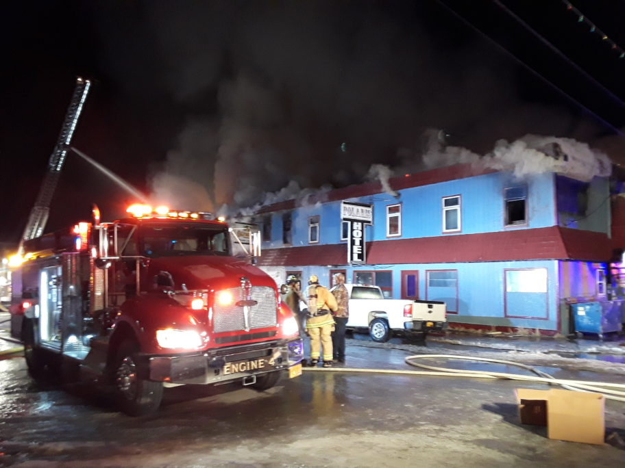 Firefighter crews on duty as Polaris Hotel continues to burn due to a fire that started in liquor store. Photo Credit: Davis Hovey, KNOM (2017)