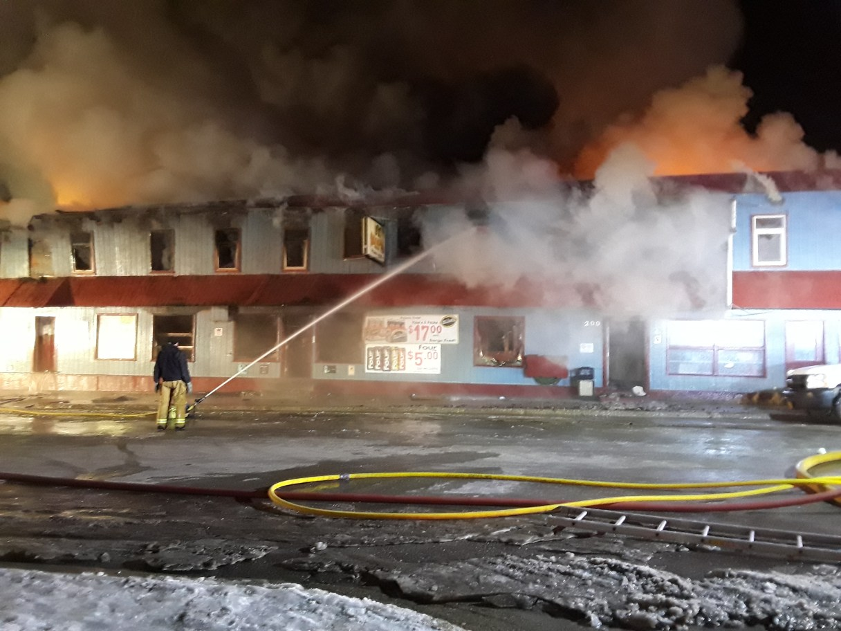 One Nome firefighter hoses down the Polaris Hotel on Tuesday morning after fire has been burning for more than 6 hours. Photo Credit: Davis Hovey, KNOM (2017)