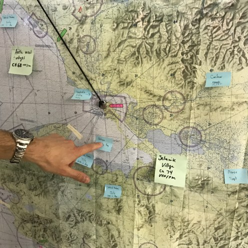A Coast Guard pilot points to a large map covered with sticky notes marking the location of wildlife. The Coast Guard receives regular updates from government scientists to avoid disturbing game during training exercises.