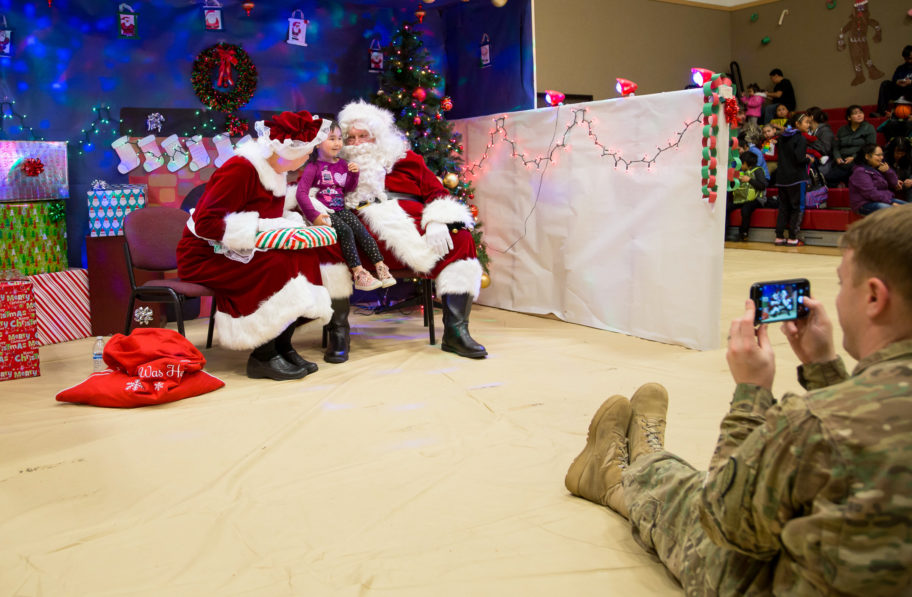 A St. Michael child meets with Santa and Mrs. Claus while a National Guard member snaps a photo.