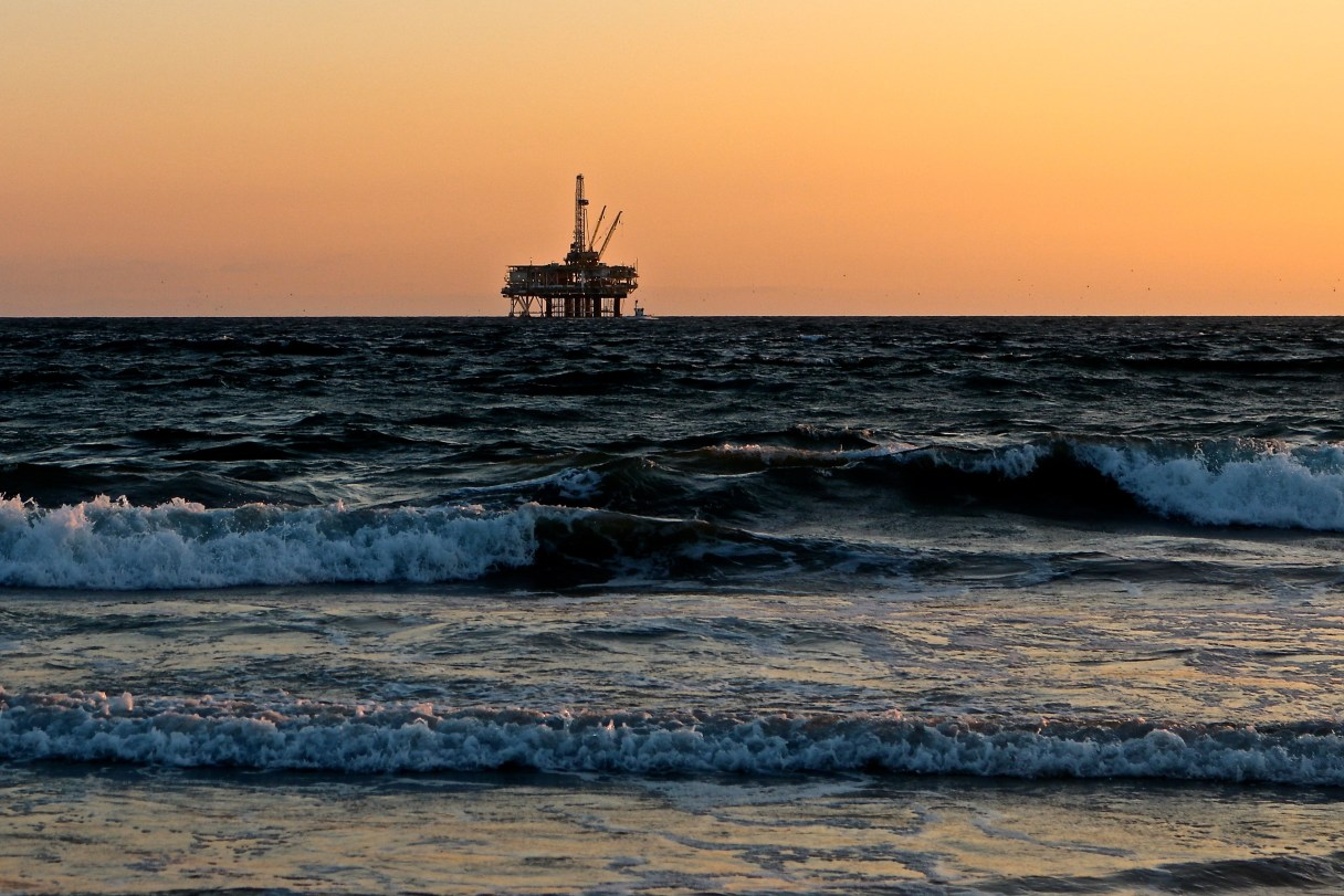 Offshore oil rig, viewed in the distance from the shore with waves crashing in the foreground