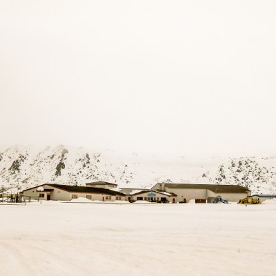 A snowy landscape, distant snowy mountains, low-hanging fog, and a modern school complex in the middle-ground.