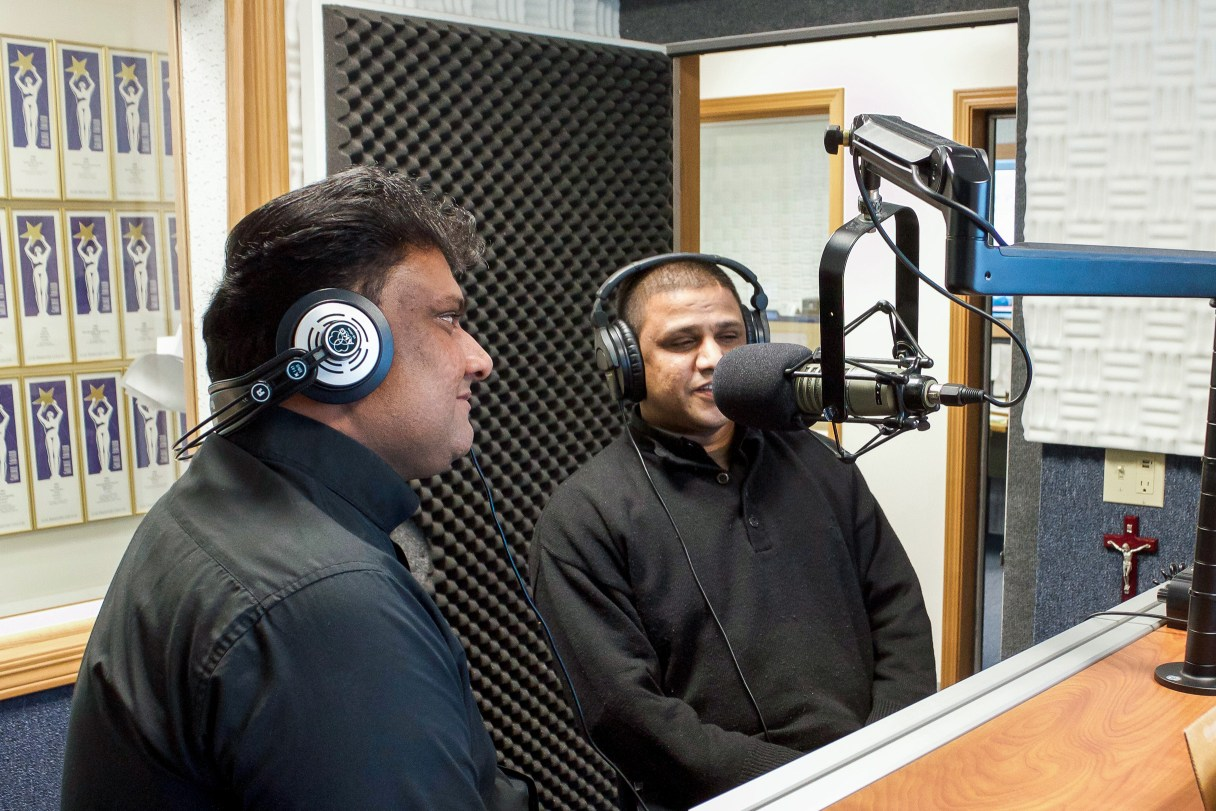 Two priests wearing headphones sit in front of a radio microphone.