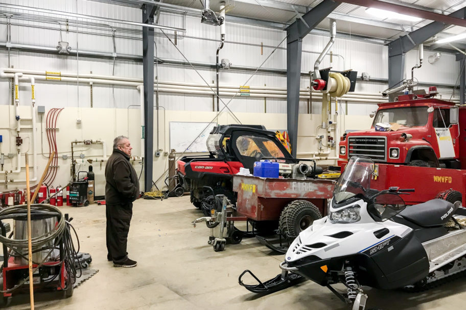 Dan Harrelson stands inside a large garage, looking at an assortment of large vehicles in front of him, including a fire truck and several all-terrain vehicles.