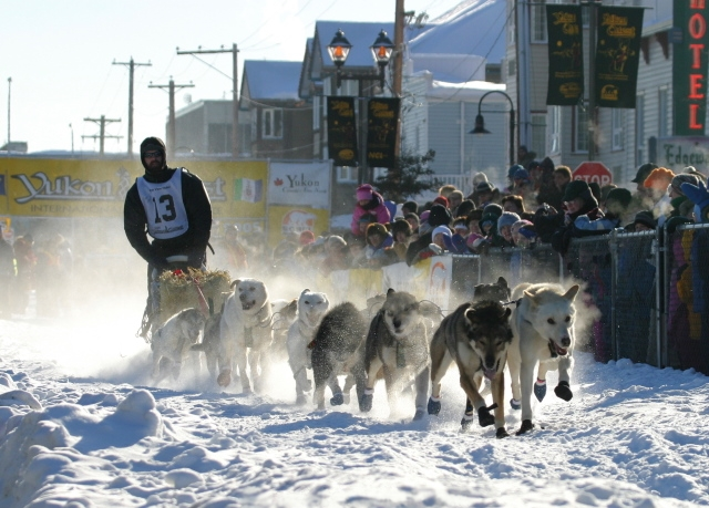 A dog team and musher race out of the finish chute, with people cheering them on