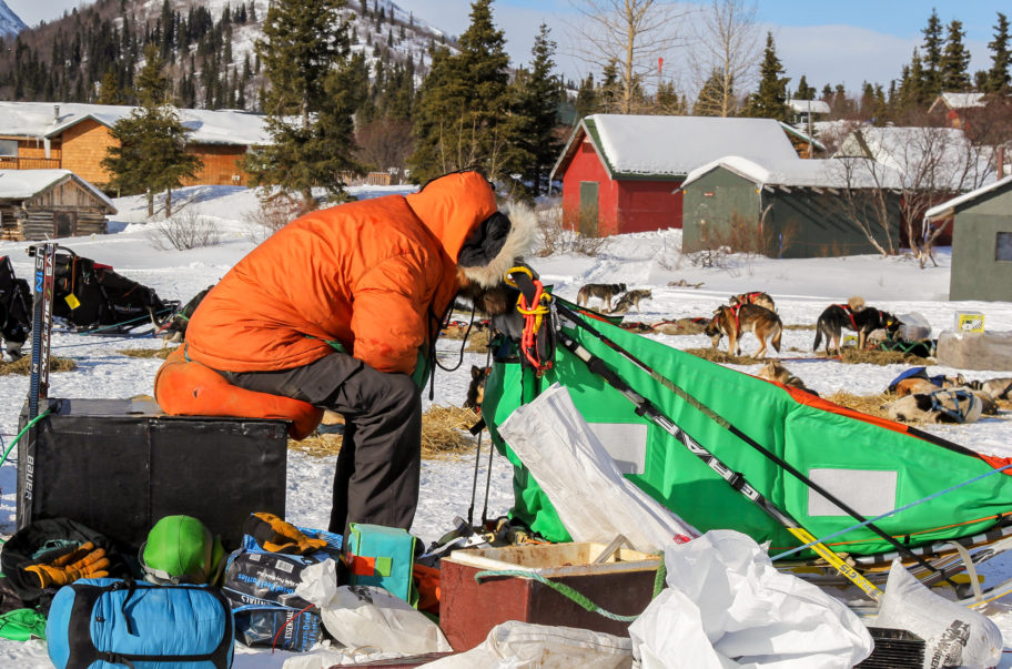 Musher in orange parka takes a short nap in a snowy Iditarod checkpoint