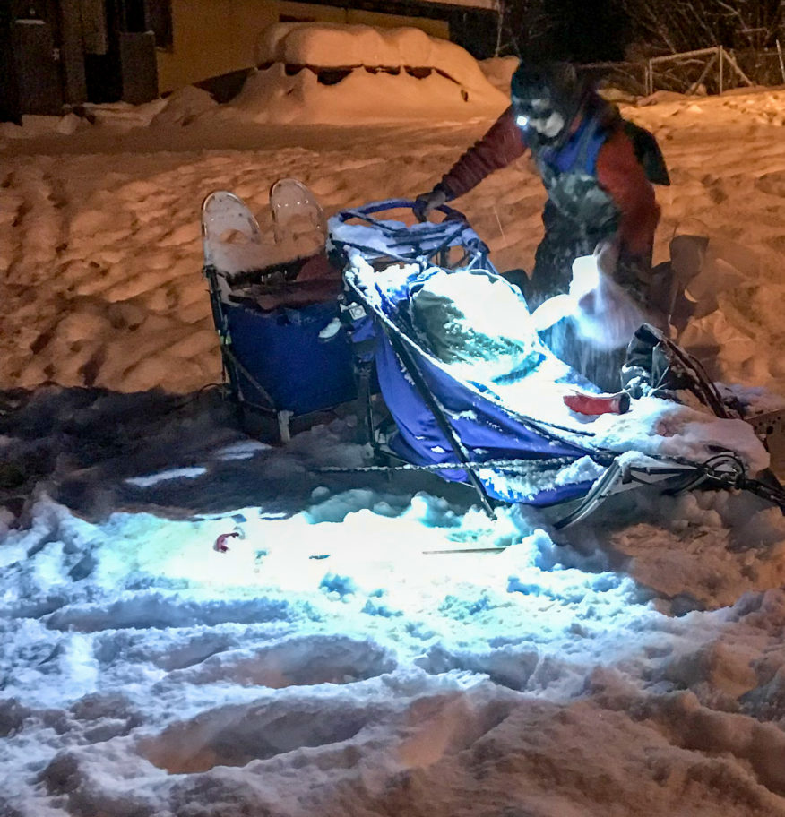 Iditarod musher examines her sled in a snowy checkpoint, at night, by the light of her headlamp.