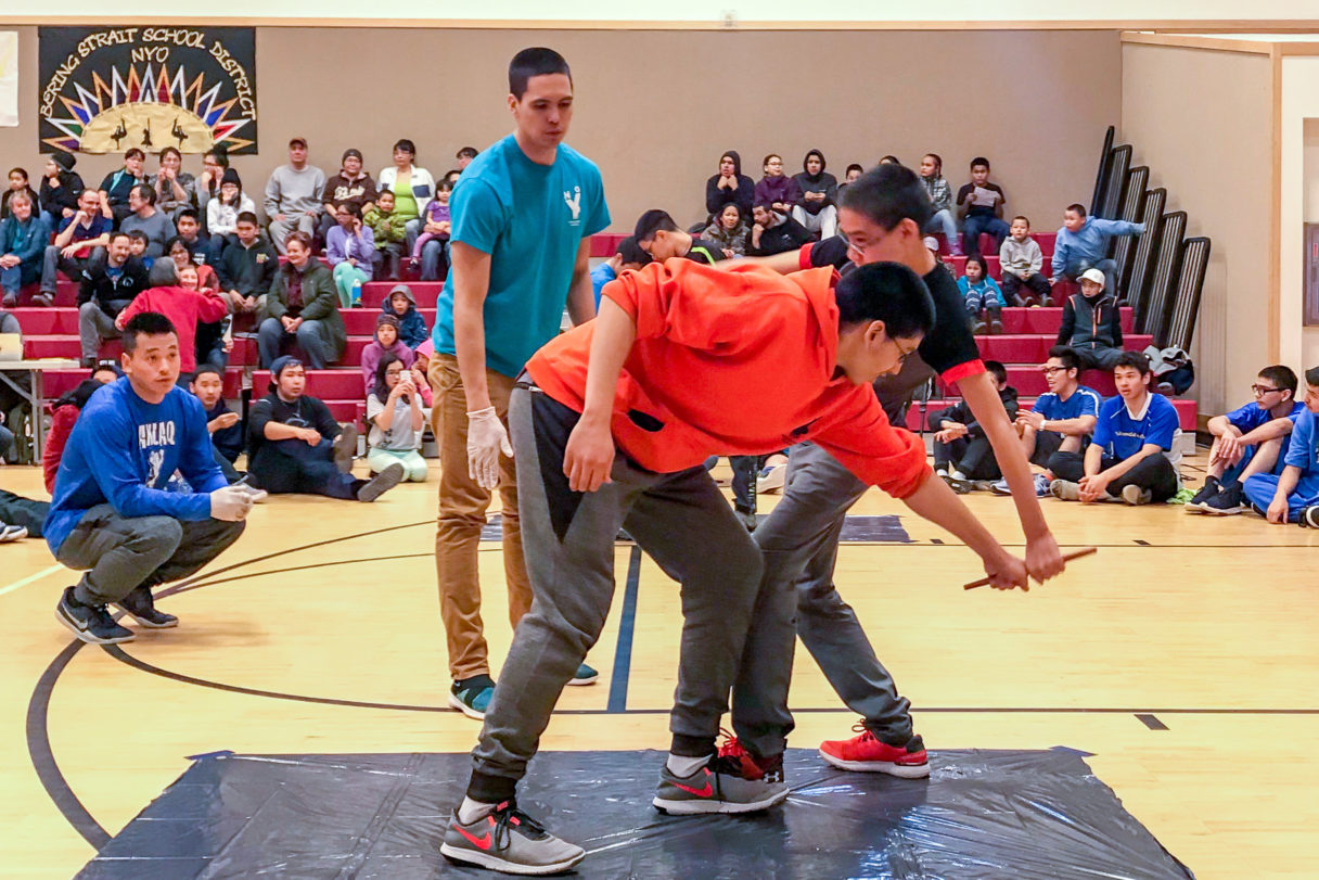 Two boys compete in the Eskimo Stick Pull inside the St. Michael school gymnasium.