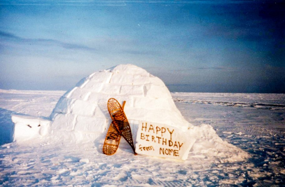 "A vintage photo of an igloo on a field of snow and ice, with a pair of snowshoes and a handwritten sign that says ""Happy Birthday from Nome."""