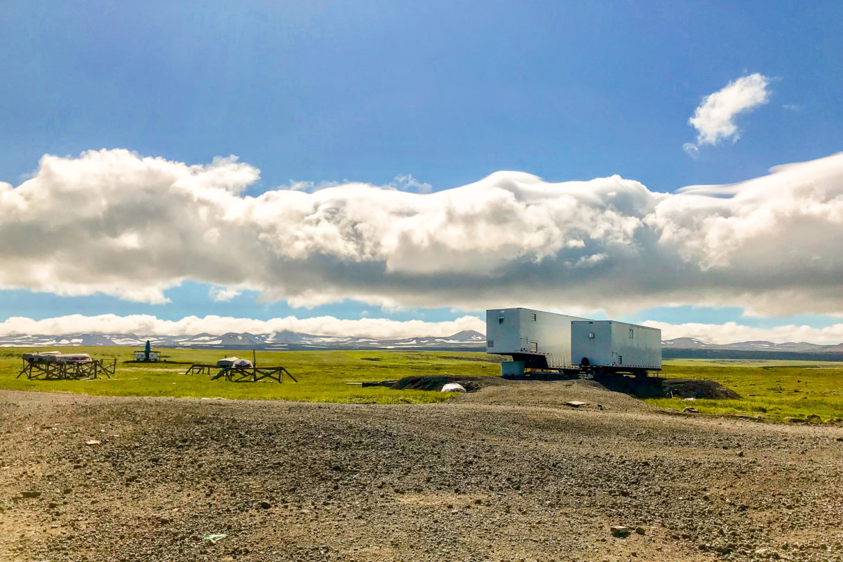 A view of the mobile reindeer processing plant in the foreground and a mountain range in the background, with a broad, green tundra landscape in between, seen on a sunny, summer day.