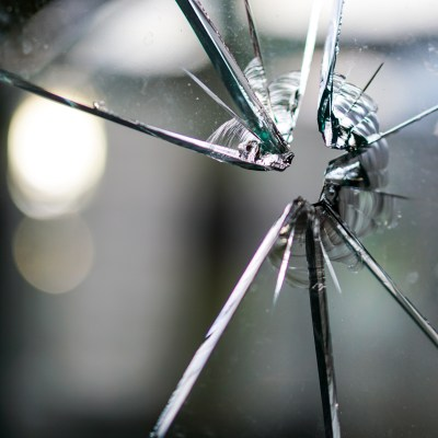 Close-up view of a broken glass window.