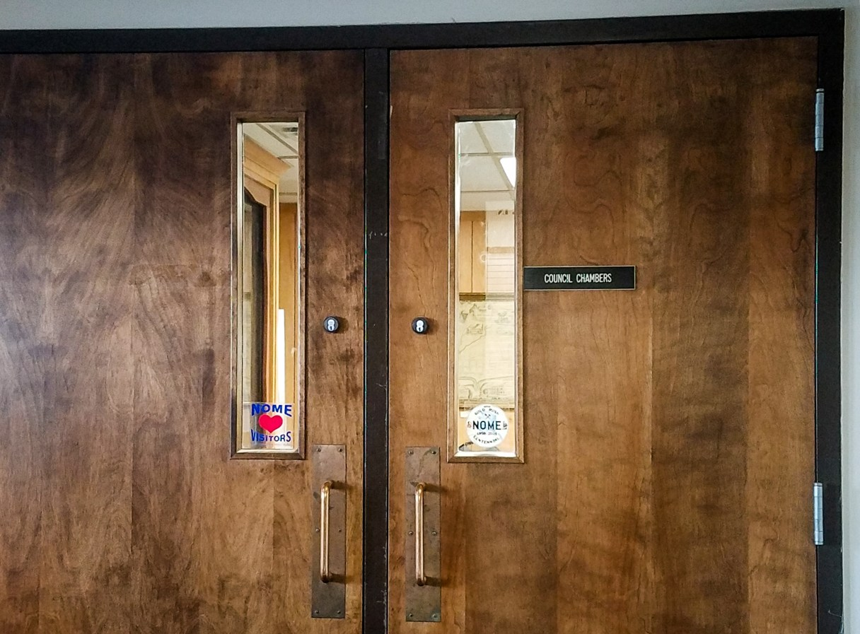 """Double doors with a small placard reading """"Council Chambers."""""""