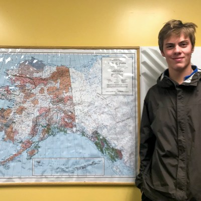 Young man wearing black windbreaker jacket stands smiling next to framed map of Alaska.