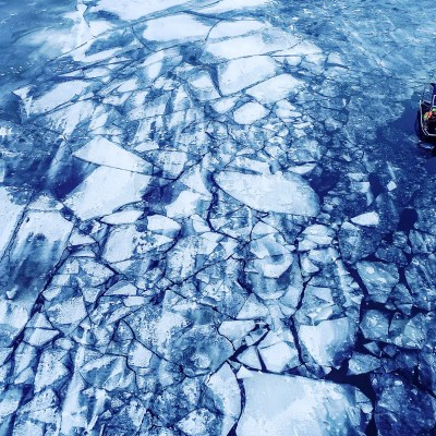 Aerial image of dark blue water, a field of ice chunks, and a small vessel involved in search-and-rescue efforts.
