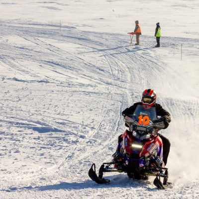 Snowmachine racer speeds up snow ramp, racing off of Bering Sea ice.