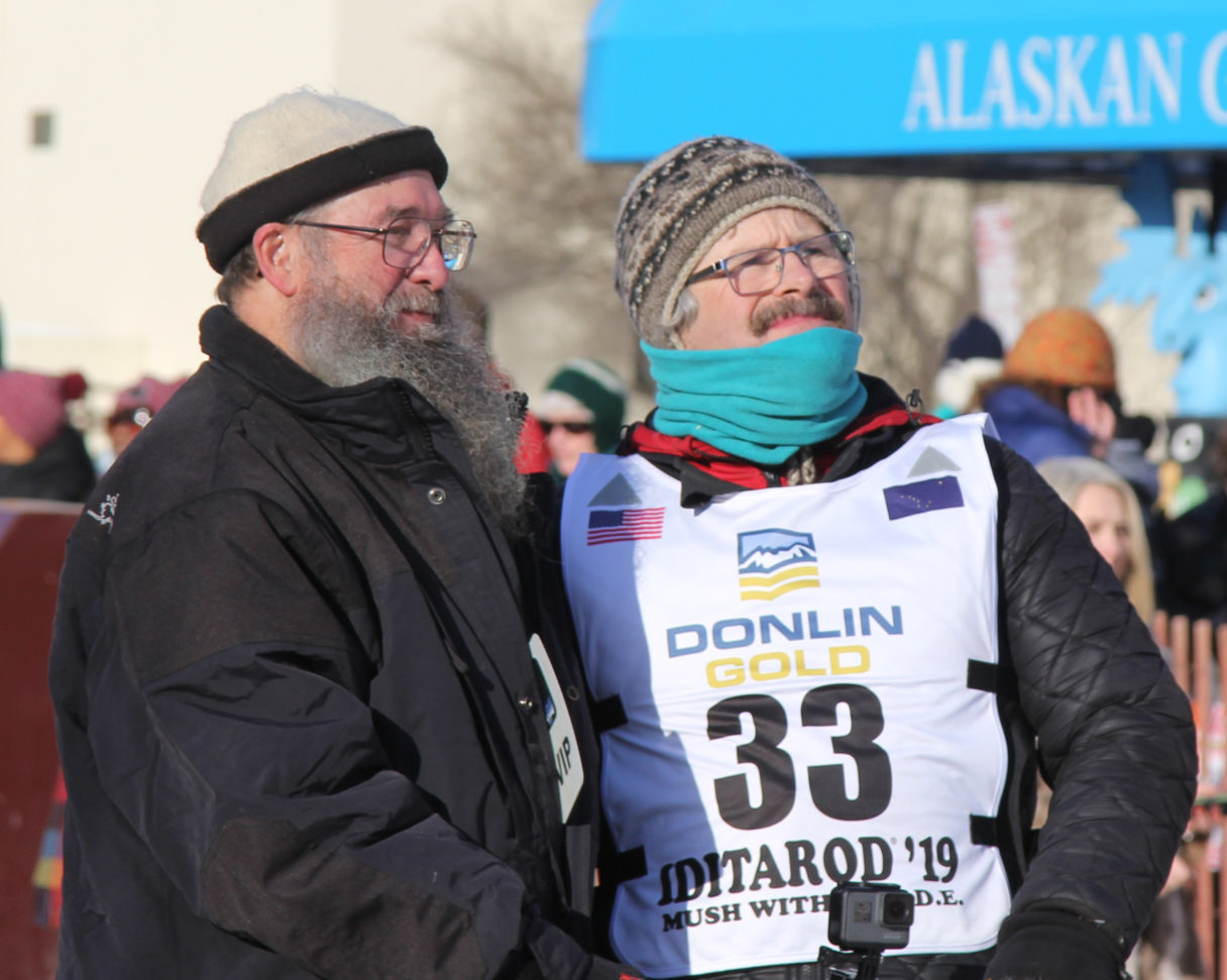 Iditarod competitor stands outside in black parka and official race bib