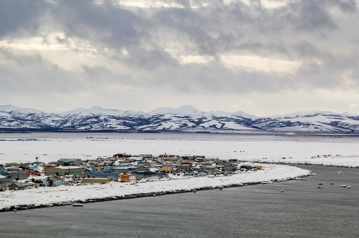 Aerial view of Unalakleet during winter, with open water along the coast.