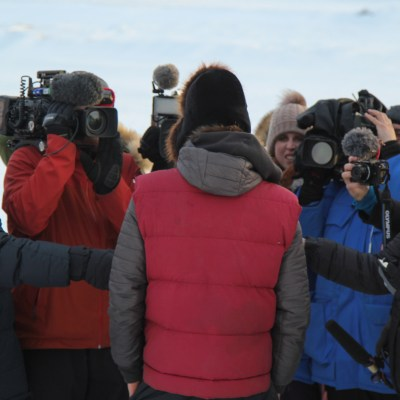 Musher in red vest, seen from behind, answers questions to a large group of closely-gathered reporters, many holding cameras or microphones.