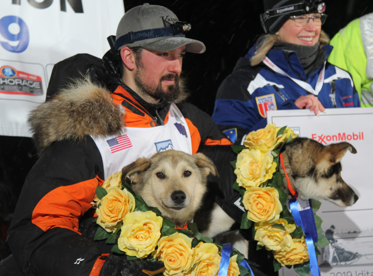 Pete Kaiser sits with his lead dogs on his lap; his dogs are wearing wreaths of yellow roses.