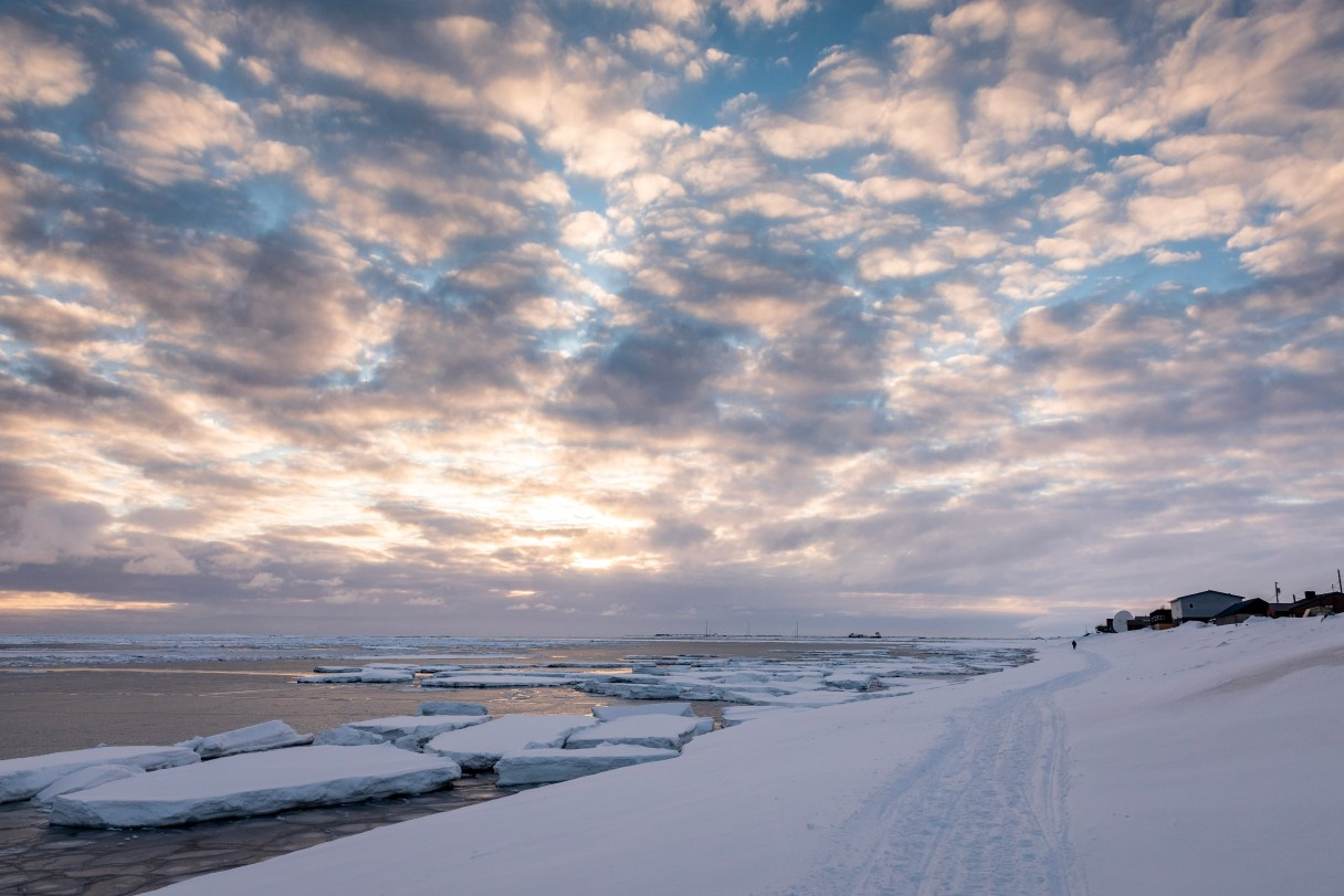 Sunset over a snowy shoreline with small icebergs dotting the ocean, stretching to the horizon