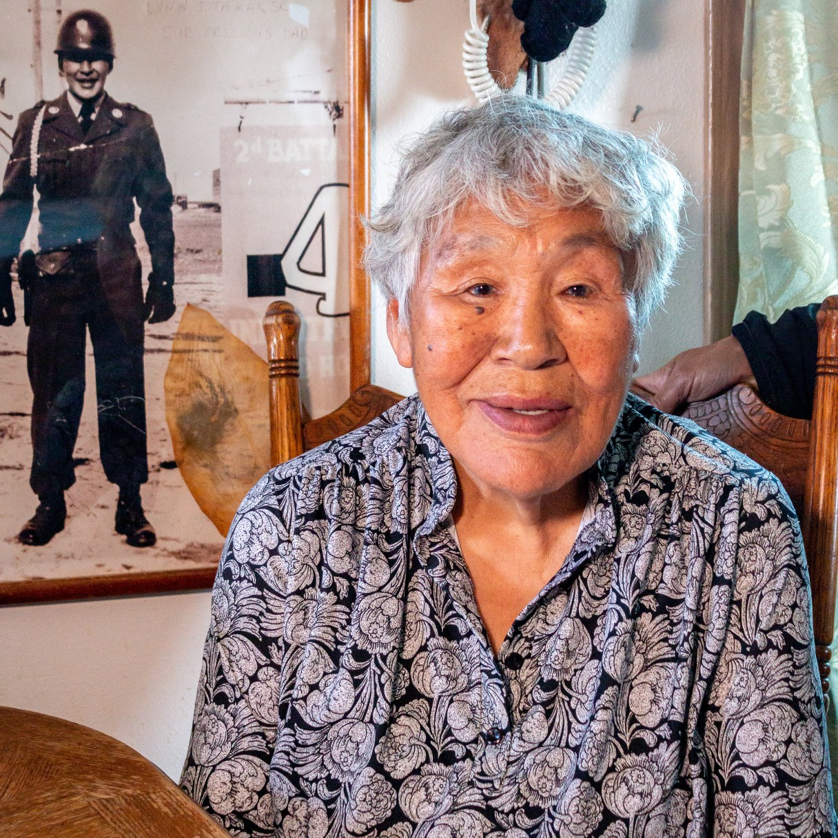 Elderly woman wearing floral-print shirt sits at table with black-and-white photo of man in uniform framed on wall behind her.