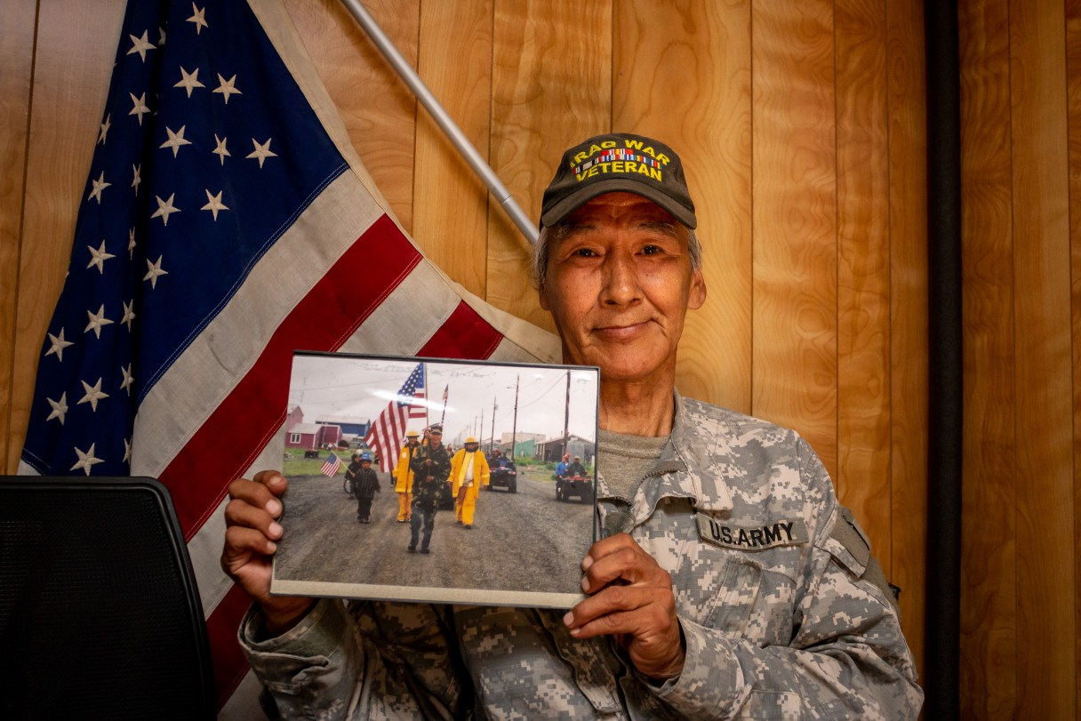 Man in Army uniform holds photo in front of American flag and wood-paneled wall