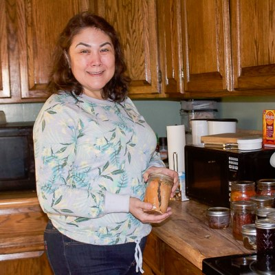 Janice Wilson holds a jar of canned salmon in the kitchen of Kugzruk Kommons.