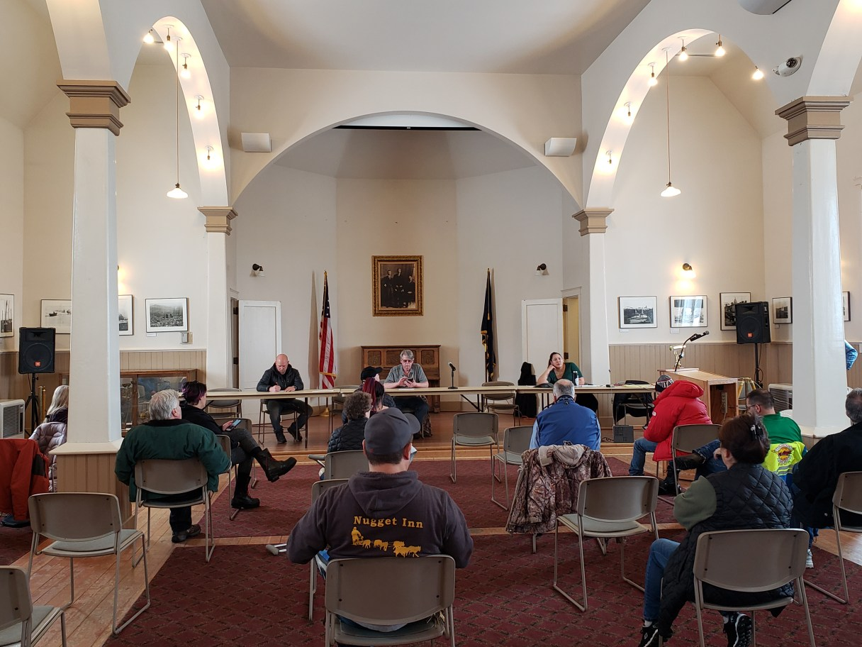 Group of people sitting in chairs have a meeting in church building.