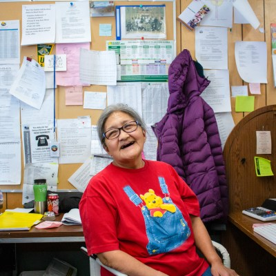 A picture of Virginia Washington, grant writer for St. Michael, smiling at her desk with a lot of notes on the wall behind her.