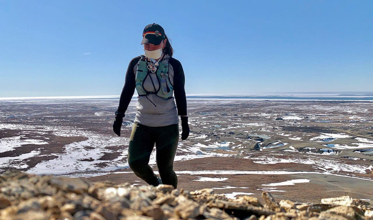 Long-distance runner Carol Seppilu training in the mountains near Nome. The mask she wears covers the part of her face damaged in her suicide attempt. (Photo from Carol Seppilu, used with permission, 2020.)