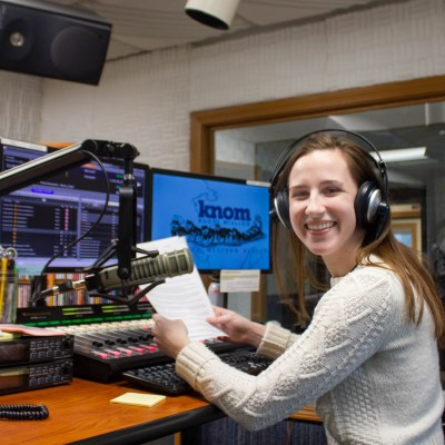 Smiling woman sits in front of a microphone in a radio studio.
