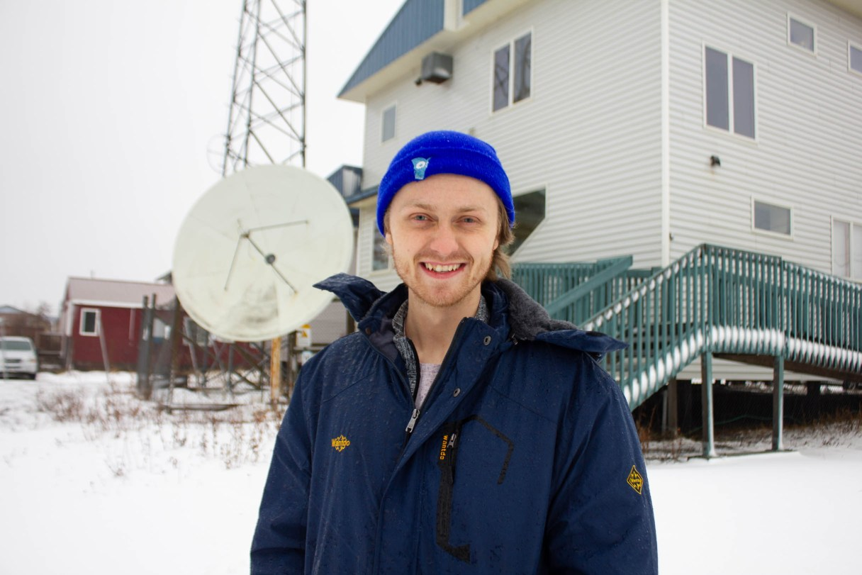 Man stands in snow in front of a radio tower.