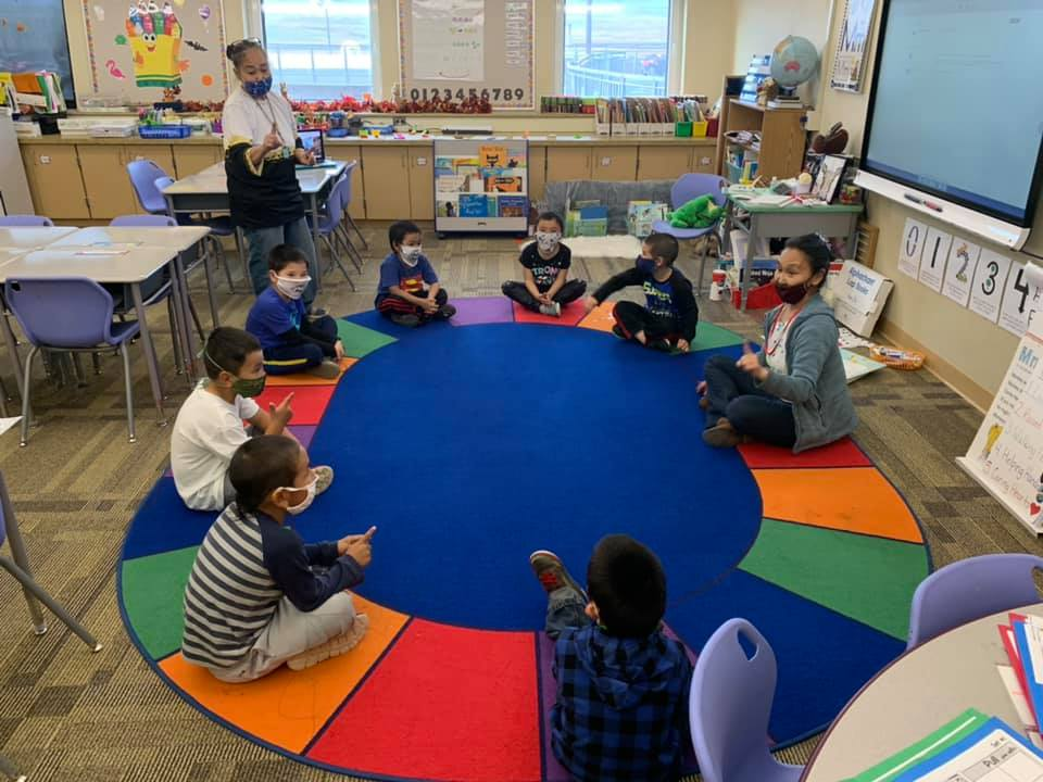 Young children sitting in a circle in a classroom