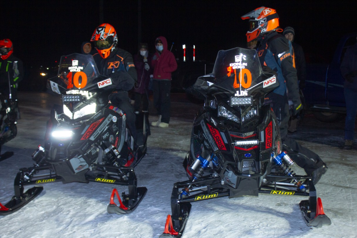 Two men on snow machines at nightime.