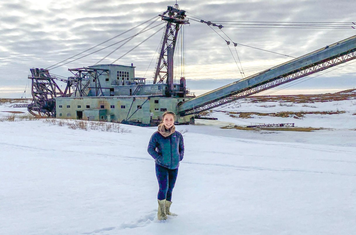 Katie Smith standing in front of a dredge in winter