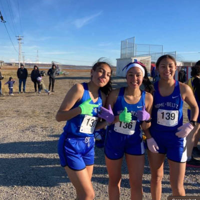 Three Nome girl athletes posing for a picture outside in the track uniforms.