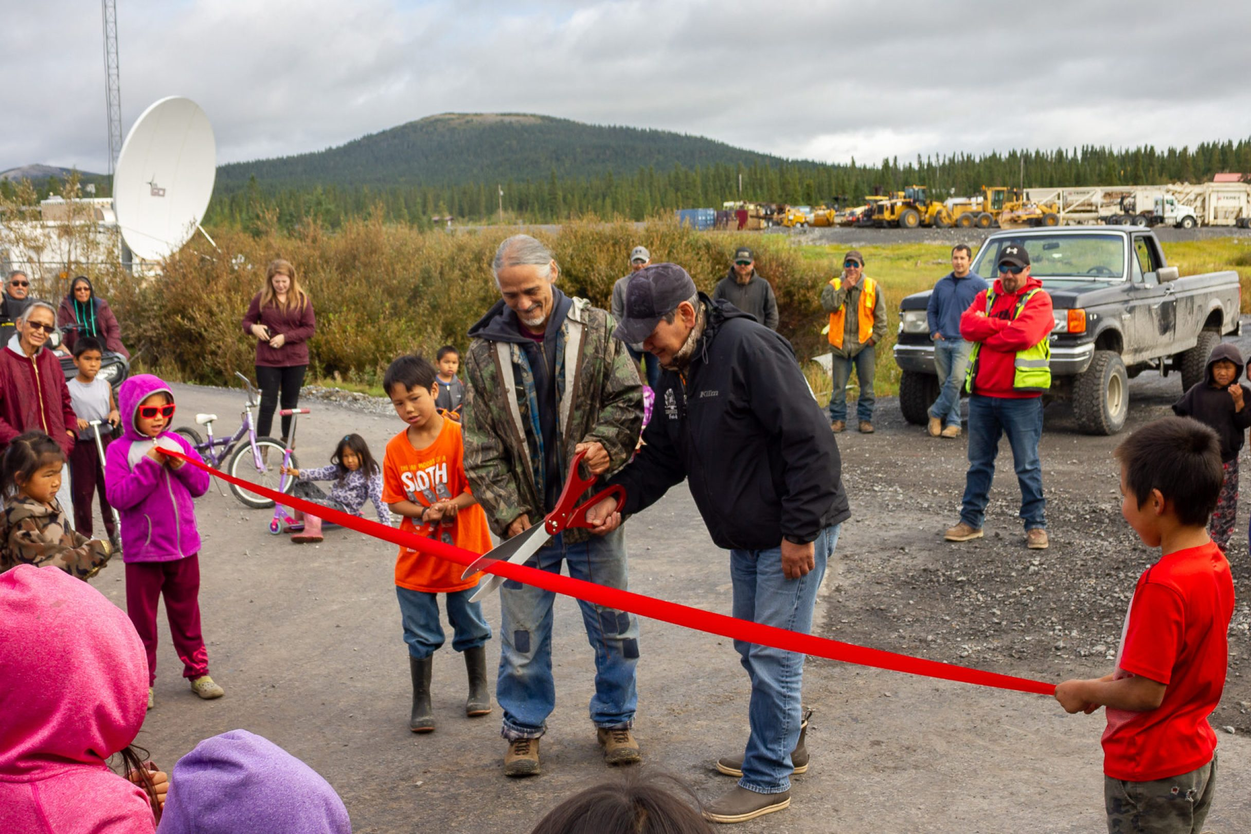Dignitaries cut a ribbon before a gathered crowd in a small Alaska community