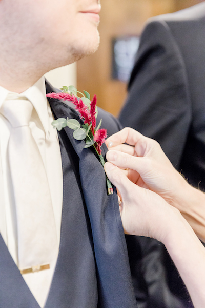 Groom boutonniere being put on