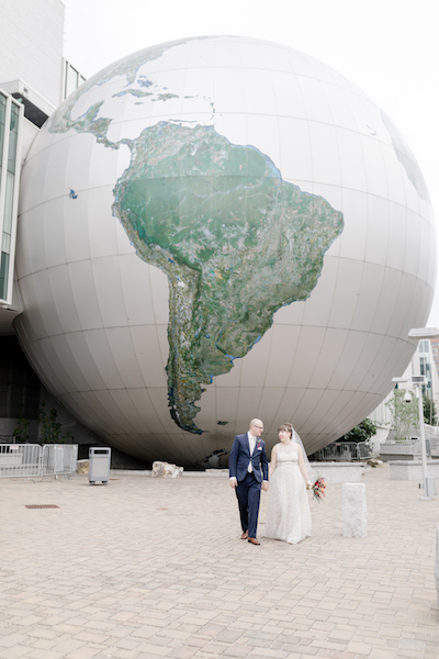 Bride and groom in front of globe at NC Museum of Natural Sciences