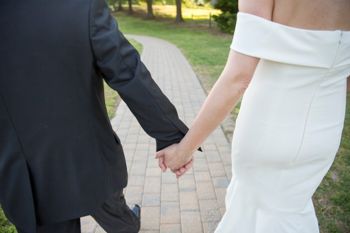 couple holding hands at a raleigh wedding