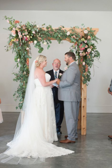 bride-groom-framed-arbor-flowers