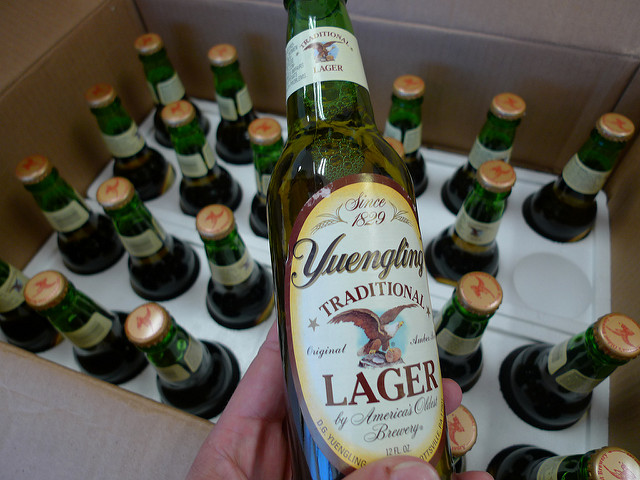 Someone holding an unopened bottle of Yuengling lager, with an entire case in the background.